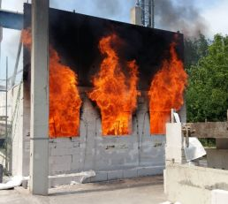 Figure 4. Fire test with natural fire according to scenario 2. The loaded test element was the ceiling of the fire compartment. Also note the simplified facade element on top of the fire compartment. This mock-up façade was used to characterize the external flaming out from the openings of the compartment.